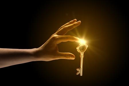 Nahaufnahme der menschlichen Hand fangen goldenen Schlüssel Standard-Bild - 32972139