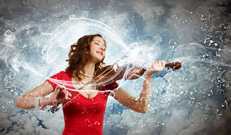 Young pretty woman in red dress playing violin photo