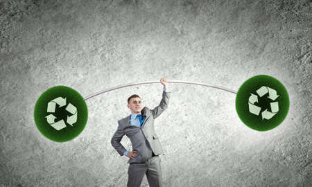 Young businessman lifting barbell with recycle signs photo