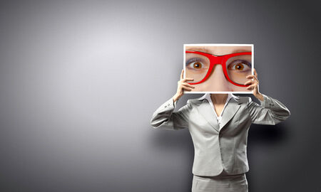 Unrecognizable businesswoman holding big photo with eyes photo