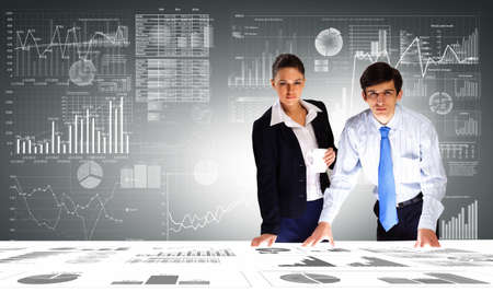 Young businessman and businesswoman discussing financial report photo