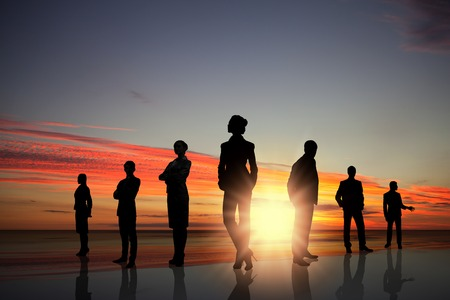 Silhouettes of business people against sunset landscape photo
