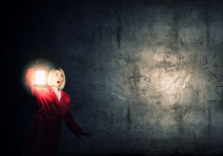 Young blonde in red cloak with lantern in darkness photo