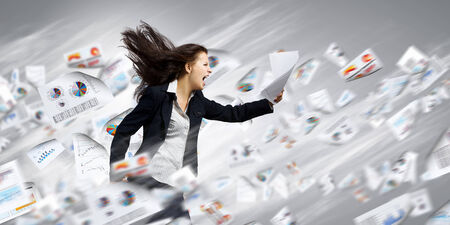 overcome a challenge: Young determined businesswoman walking against strong wind Stock Photo