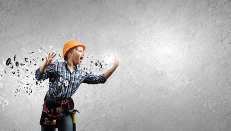 Young woman builder screaming emotionally in mobile phone photo