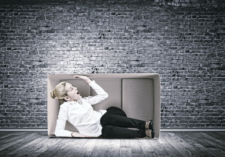 are trapped: Young emotional woman trapped in carton box Stock Photo