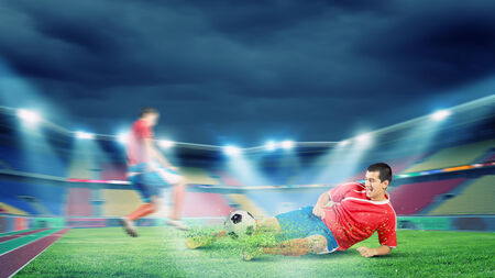 Two football player fighting for ball at stadium photo