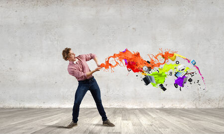 Young emotional man pulling colorful paint splashes photo
