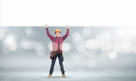 Young builder man in hardhat holding white blank banner photo