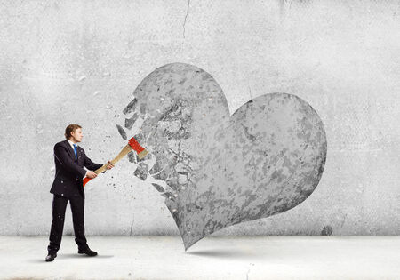 Young determined businessman crashing stone heart with axe photo