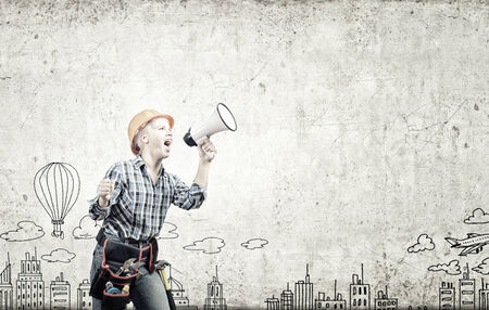 Young woman in hardhat screaming in megaphone photo