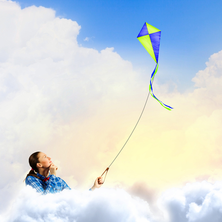 Young woman in casual playing with kite photo