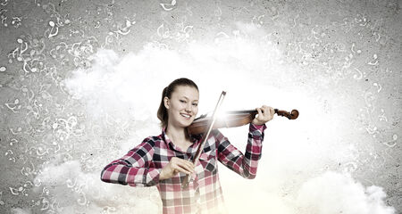 Young pretty girl in casual playing violin photo