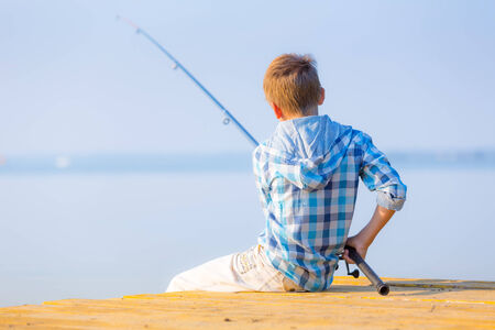 Boy in blue shirt sit on a pier with a fishing rod by the sea photo
