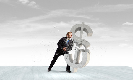 Young businessman breaking stone dollar sign. Currency concept photo