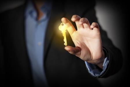 金色の鍵を引く人間の手のクローズ アップ