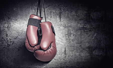 thai boxing: Pair of red boxing gloves hanging on wall