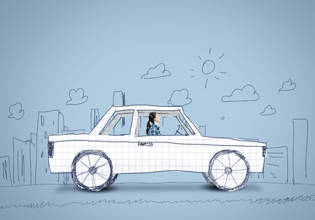 Young girl driving car made of paper Stock Photo