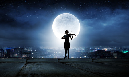 woman violin: Silhouette of woman playing violin at night Stock Photo