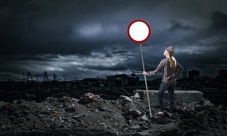 Young girl in casual holding stop sign photo