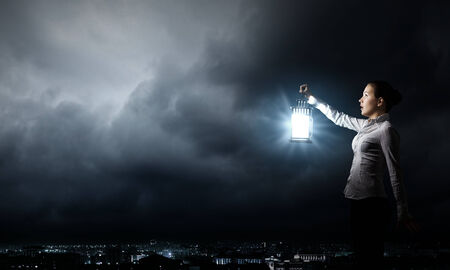 Young pretty businesswoman with lantern in darkness photo