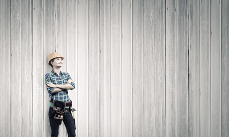 toolbelt: Young woman builder in hardhat wearing toolbelt Stock Photo
