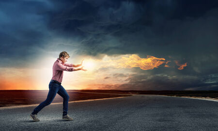 supernatural power: Young man in casual throwing magic fire balls