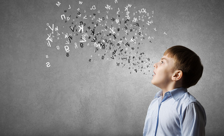 Cute boy of school age and letters flying around photo