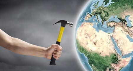 demografia: Cierre de martillo en la mano del hombre que golpea el planeta Tierra.
