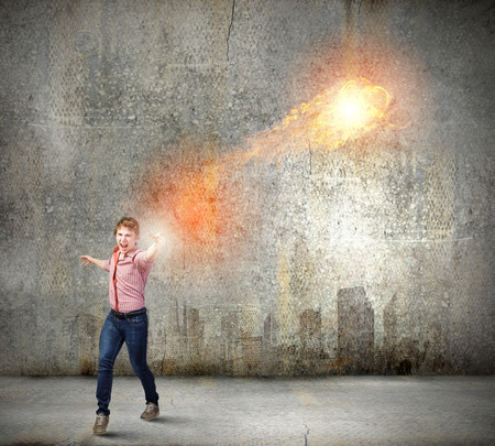conjuring: Young man in casual throwing magic fire balls