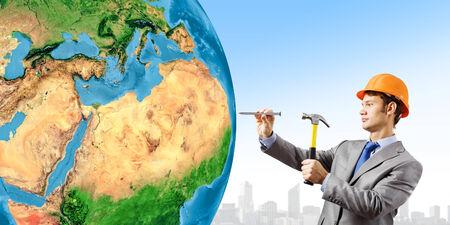 Businessman in helmet hammering nail in Earth planet Stock Photo