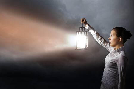 seeking solution: Young businesswoman walking in darkness with lantern in hand