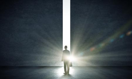 puerta abierta: Vista trasera del hombre de negocios de pie en la luz de paso en la pared