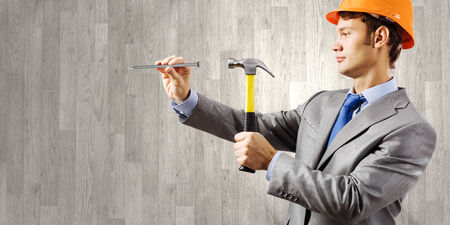Young businessman in suit and hardhat hammering nail in wall Stock Photo