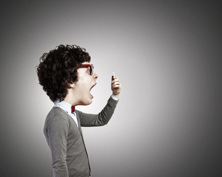 head phone: Funny young man with big head screaming emotional in mobile phone Stock Photo