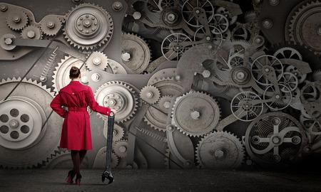 Jonge vrouw in rode jas bevestigingsmechanisme met moersleutel