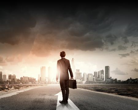 vision futuro: Vista trasera del hombre de negocios con maleta que se coloca en la carretera