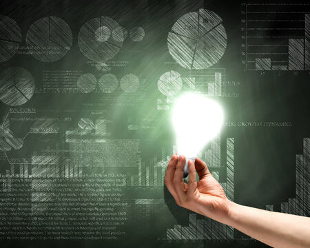 financial concept: Close up of hand holding light bulb with sketches at background