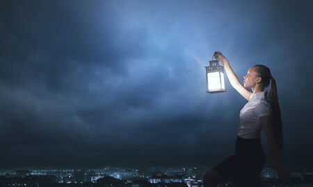 business solutions: Young businesswoman walking in darkness with lantern in hand