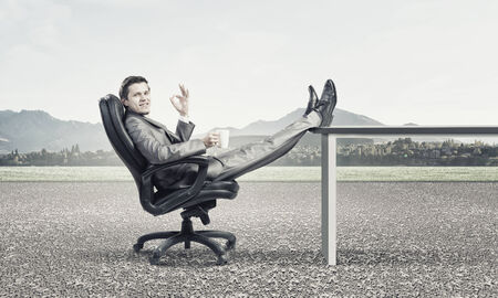 Young confident businessman sitting in chair with mug in hands photo