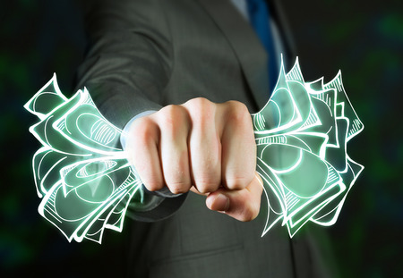 close fist: Close up of businessman grasping dollar banknotes in fist