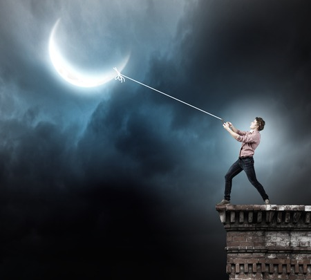 man in the moon: Young man in casual catching moon with rope Stock Photo