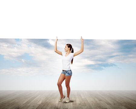 Young pretty girl in shorts holding white blank banner photo