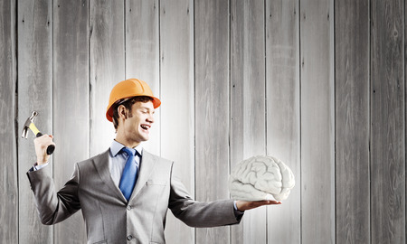 self discovery: Young businessman with hammer and human brain in hand