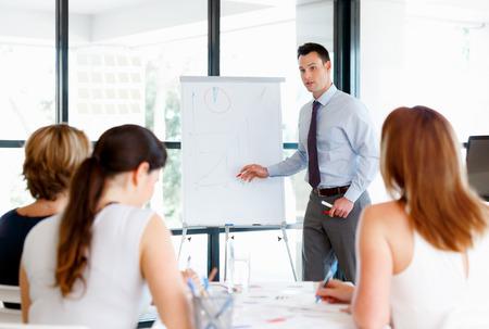 personas dialogando: Hombre de negocios haciendo una presentaion delante de sus colegas
