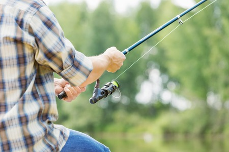 fishing rods: Close up of guy sitting on bridge and fishing