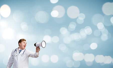 emotionally: Young male doctor screaming in megaphone emotionally Stock Photo
