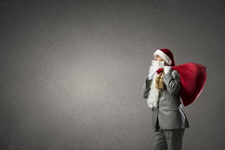 Businessman in Santa hat with red gift bag behind back photo