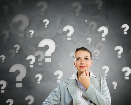 asking question: Portrait of pretty young businesswoman and many question marks around Stock Photo