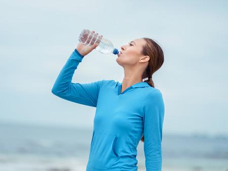 tomando agua: Joven deportiva de agua potable en la costa del mar Foto de archivo